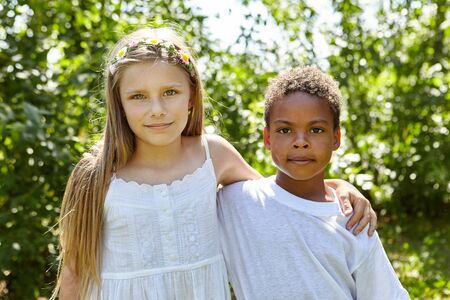 African boy is standing next to a blonde girl in the garden