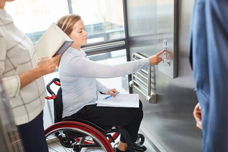 Young woman in a wheelchair presses a button in the elevator in the company or university