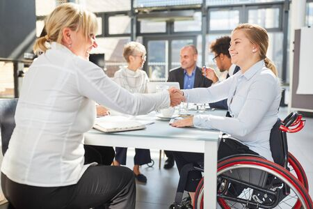 Businesswoman and colleague in a wheelchair handshaking in a business meeting Stock Photo