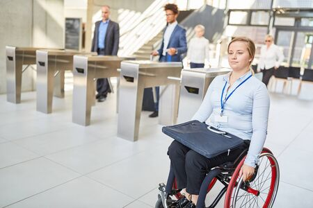 Young businesswoman in wheelchair on the way to the office with access control