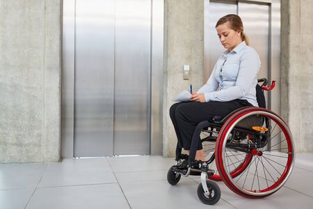 Young woman in a wheelchair in front of an elevator in the company as an inclusion concept Stock Photo