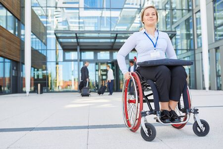 Businesswoman in a wheelchair in front of the office looks forward to conference on inclusion