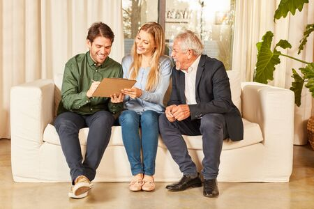 Happy broker and young couple as tenants signing the lease