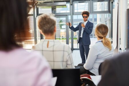 Blind businessman as speaker at business meeting in front of a group of listeners