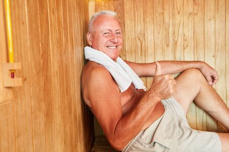 Smiling senior man as Best Ager with thumbs up in the hotel sauna