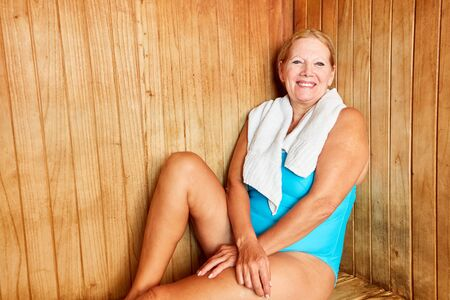 Smiling senior woman relaxing in the sauna on a spa vacation