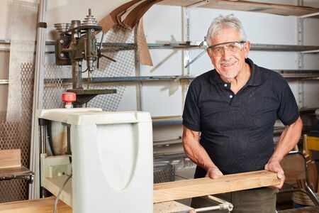 Senior as carpenter or joiner works with a beam on the planing machine