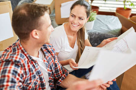 Happy young couple with construction drawing together plans new construction of house