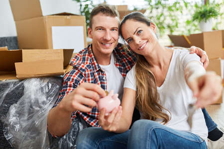 Happy couple after moving piggy bank in new home