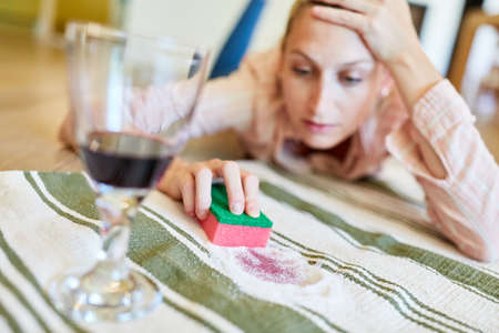 Housewife painstakingly removes the red wine stain from the carpet with salt and sponge Archivio Fotografico - 150635465