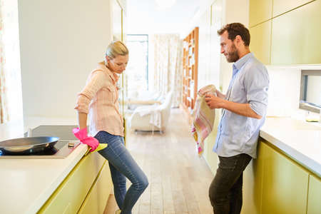 Man and housewife with frustration about role allocation while doing housework