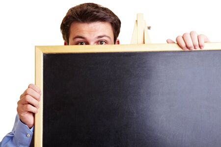 Manager with stage fright is hiding behind a blackboard Standard-Bild