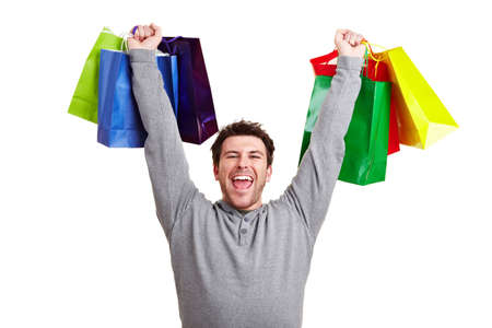 Cheering man raises his arms with colorful shopping bags