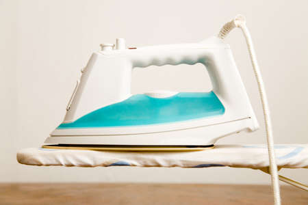 Bright iron stands on an ironing board Archivio Fotografico - 150692621