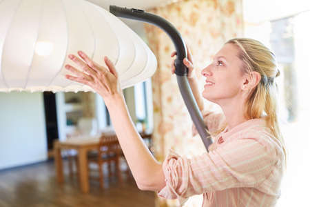 Woman as a cleaning lady or domestic help vacuuming a hanging lamp Archivio Fotografico
