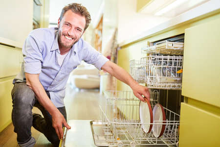 Smiling man is cleaning clean dishes. Dishwasher in the kitchen Archivio Fotografico - 150635510