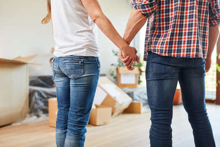 Happy couple holds on to hands in new home after moving Archivio Fotografico - 150635520