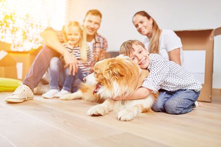Happy family with two children and dog moving to a new family home