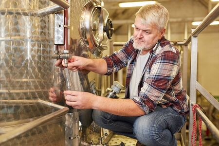 Winemaker checks fresh wine on the fermentation tank in a winery during the winemaking process