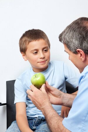 Dentist gives child a green apple