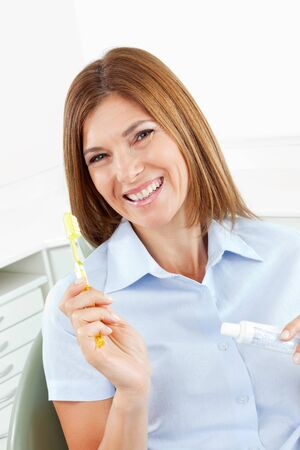 Smiling woman with toothbrush and toothpaste in dental office