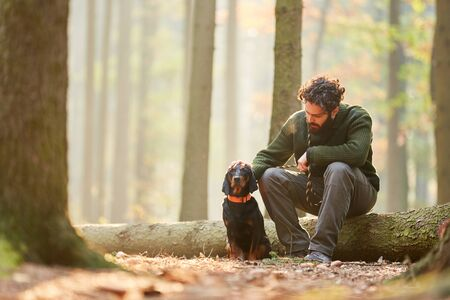 Hound as a hunting dog together with a hunter or forester take a break in the forest 免版税图像 - 150179191