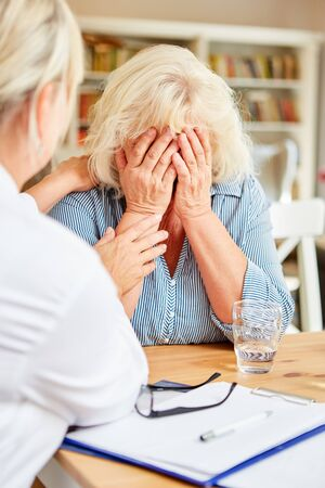 Crying old patient is comforted by a sensitive doctor during a home visit Stockfoto