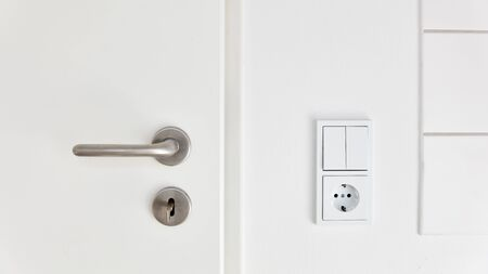 White light switch and socket next to door in kitchen or bathroom