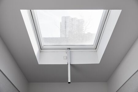 Electric skylight with daylight in the hallway from an attic