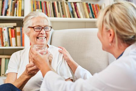 Doctor gives a remedy to a patient in a nursing home