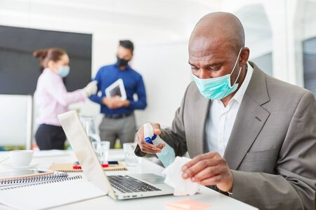 Businessman wearing mask disinfecting computer in the office because of Covid-19 and corona virus