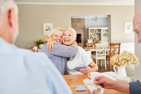 Two laughing senior women hug each other in the lounge in the retirement home