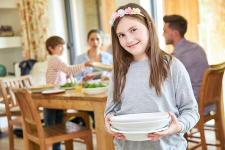 Girl helps with housework and carries dishes for lunch Archivio Fotografico