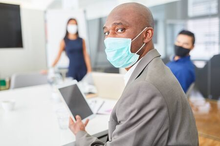 African business man with mask over Covid-19 and tablet computer in a meeting