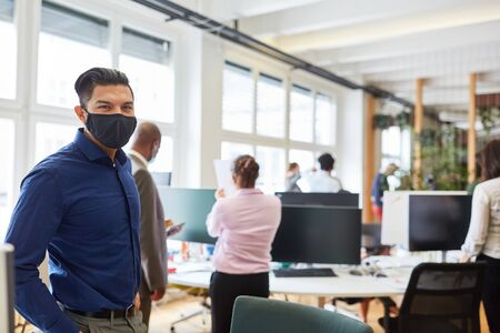 Businessman wearing face mask for Covid-19 and corona virus pandemic in open plan office