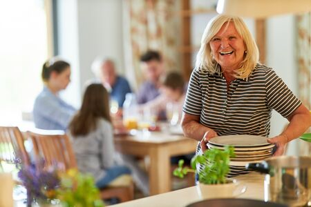 Happy grandmother with dishes in the kitchen is cooking for her extended family Reklamní fotografie