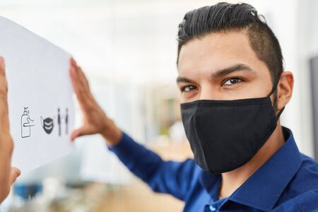 Business man with face mask fastens hygiene rules as prevention against Coronavirus and Covid-19