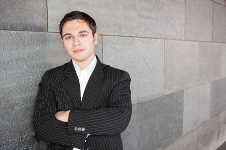 Young manager with arms crossed leaning against a wall