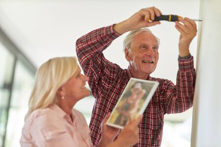 Happy seniors couple with screwdriver while photo hanging up indoors Archivio Fotografico - 150512871