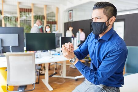 Business man with mouth-nose protection because of Covid-19 disinfect hands as prevention
