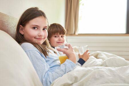 Sibling children drink orange juice for breakfast in bed in the bedroom