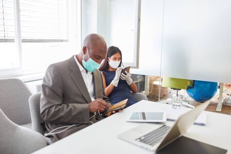 Two businessmen with face mask over Covid-19 write SMS on smartphone in the office Archivio Fotografico