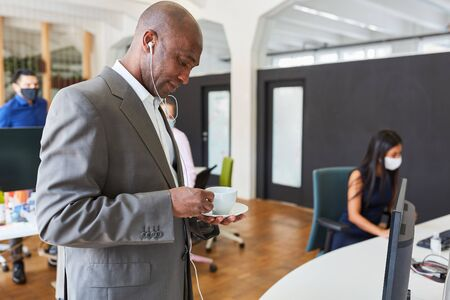 African business man in start-up office with in-ear headphones and coffee cup Archivio Fotografico - 150512889