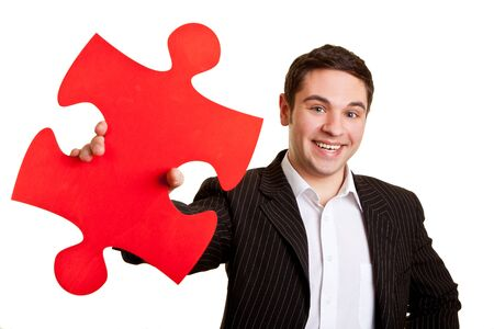 Laughing businessman holds a red puzzle piece Archivio Fotografico - 150512838