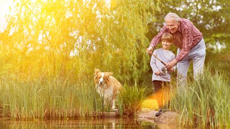 Happy child fishing with grandpa and dog by the lake in summer Archivio Fotografico - 150512847