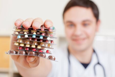 Doctor in hospital holds a stack of colorful medicines