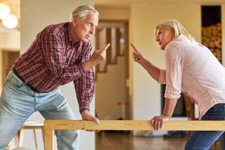 Senior couple face a quarrel with their index finger raised