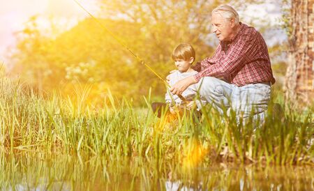 Grandpa and grandson fishing together as anglers on the lake in summer Archivio Fotografico - 150512855