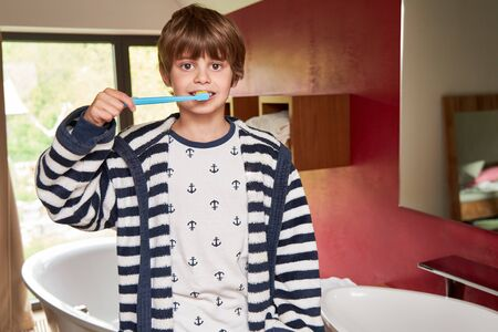 Boy in bathrobe with toothbrush brushing teeth as tooth decay Archivio Fotografico - 150512856