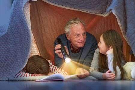 Grandpa reads grandchildren story under a blanket as a tent at home Archivio Fotografico - 150512858